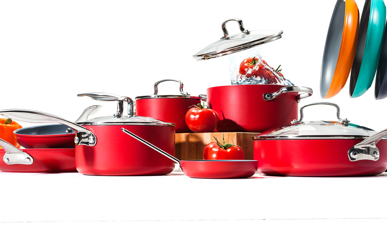 Red kitchenware with splashing tomatoes