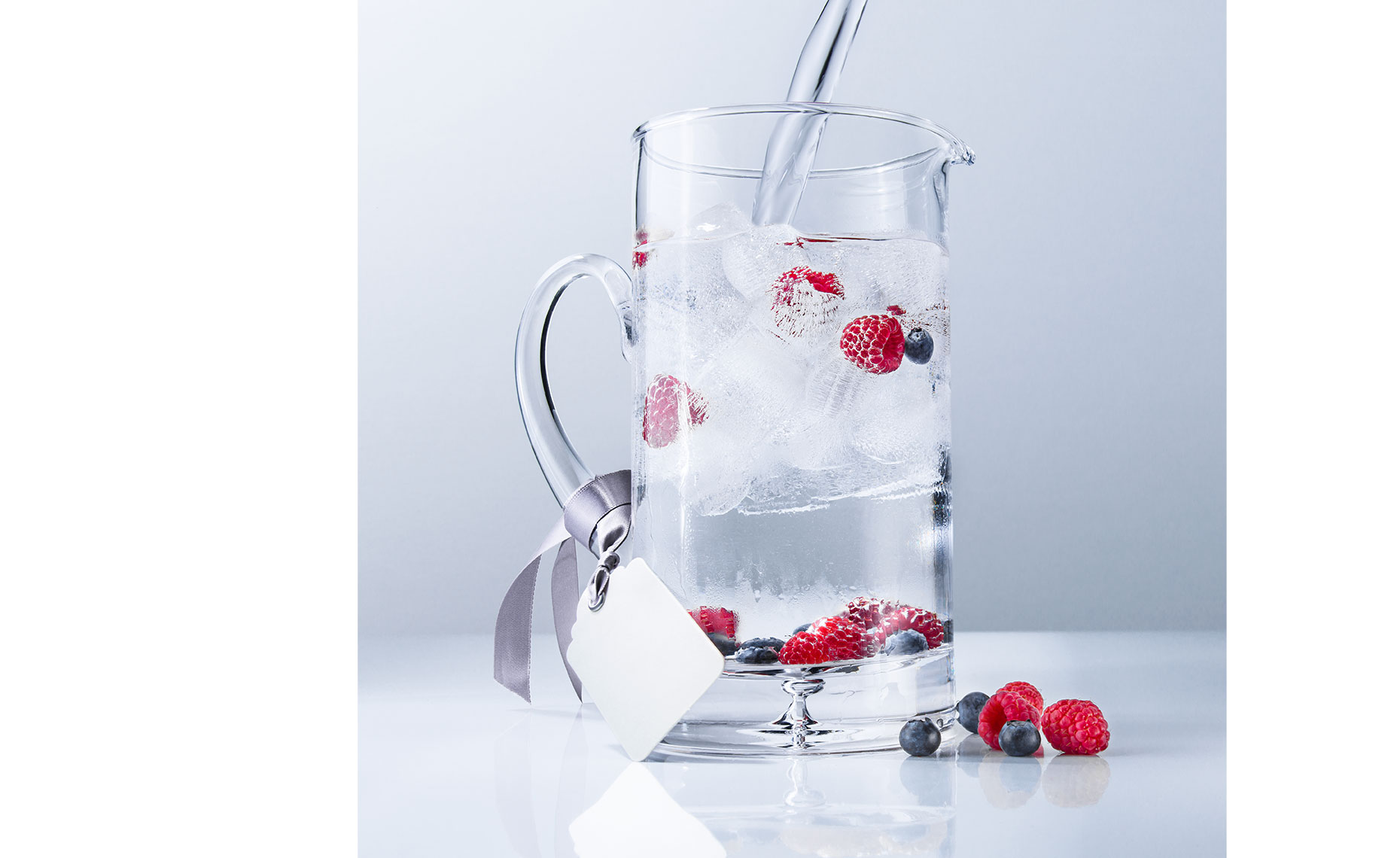 Chilled pitcher with water pour and raspberries